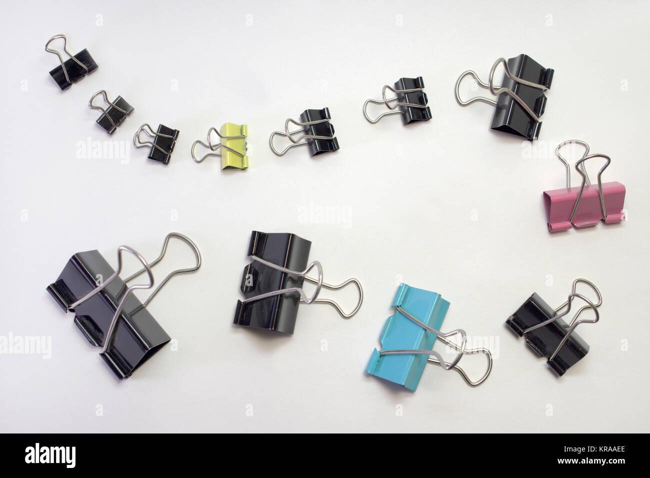 Haufen Metall binder clips für Papier, verschiedene Größen und Farben. In der Zeile festgelegt Stockfoto