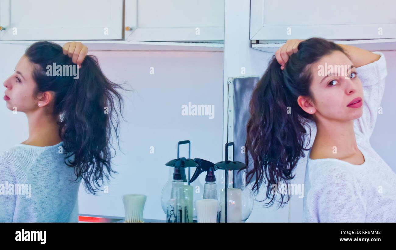 Junge Frau mit langen dunklen Haaren winkte in einem Spiegel reflektiert und in einem Pferdeschwanz durch Ihre eigene Stockbild