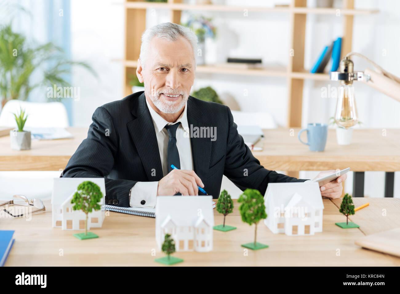 Angenehme real estate agent wartet auf seine Kollegen, während allein sitzen Stockbild