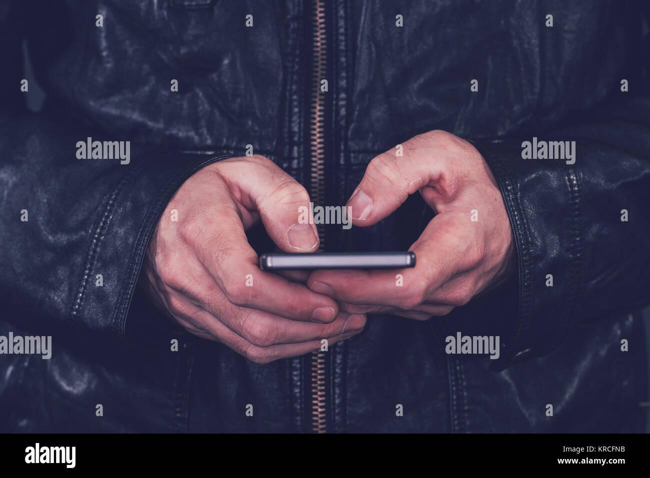 Mann in der Lederjacke mit Handy für den Versand von SMS. Moderne Technologie und lifestyle Konzept. Stockfoto
