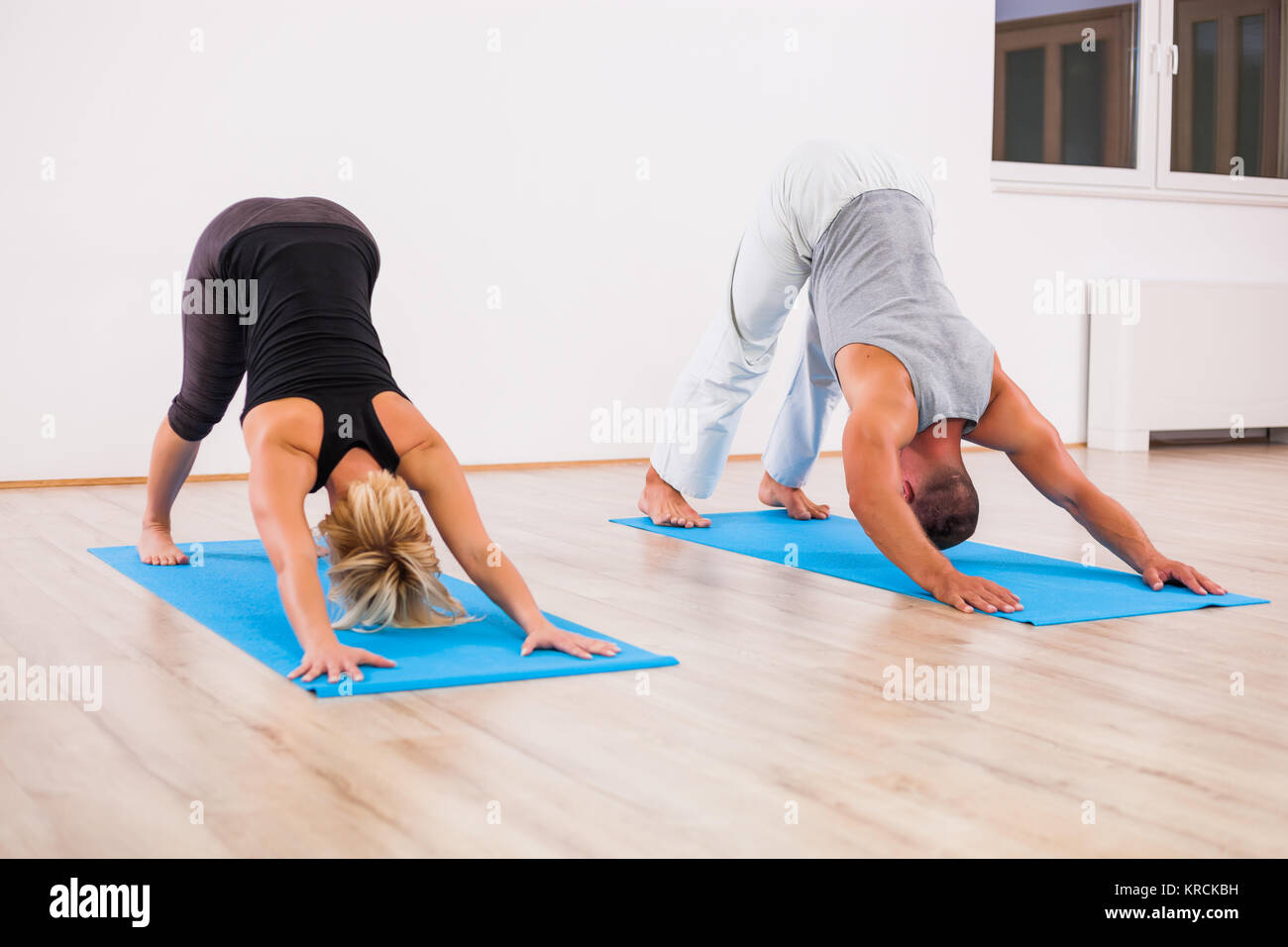 Nach Mann und Frau praktizieren von Yoga, svanasana/Nach unten schauender Hund darstellen Stockbild