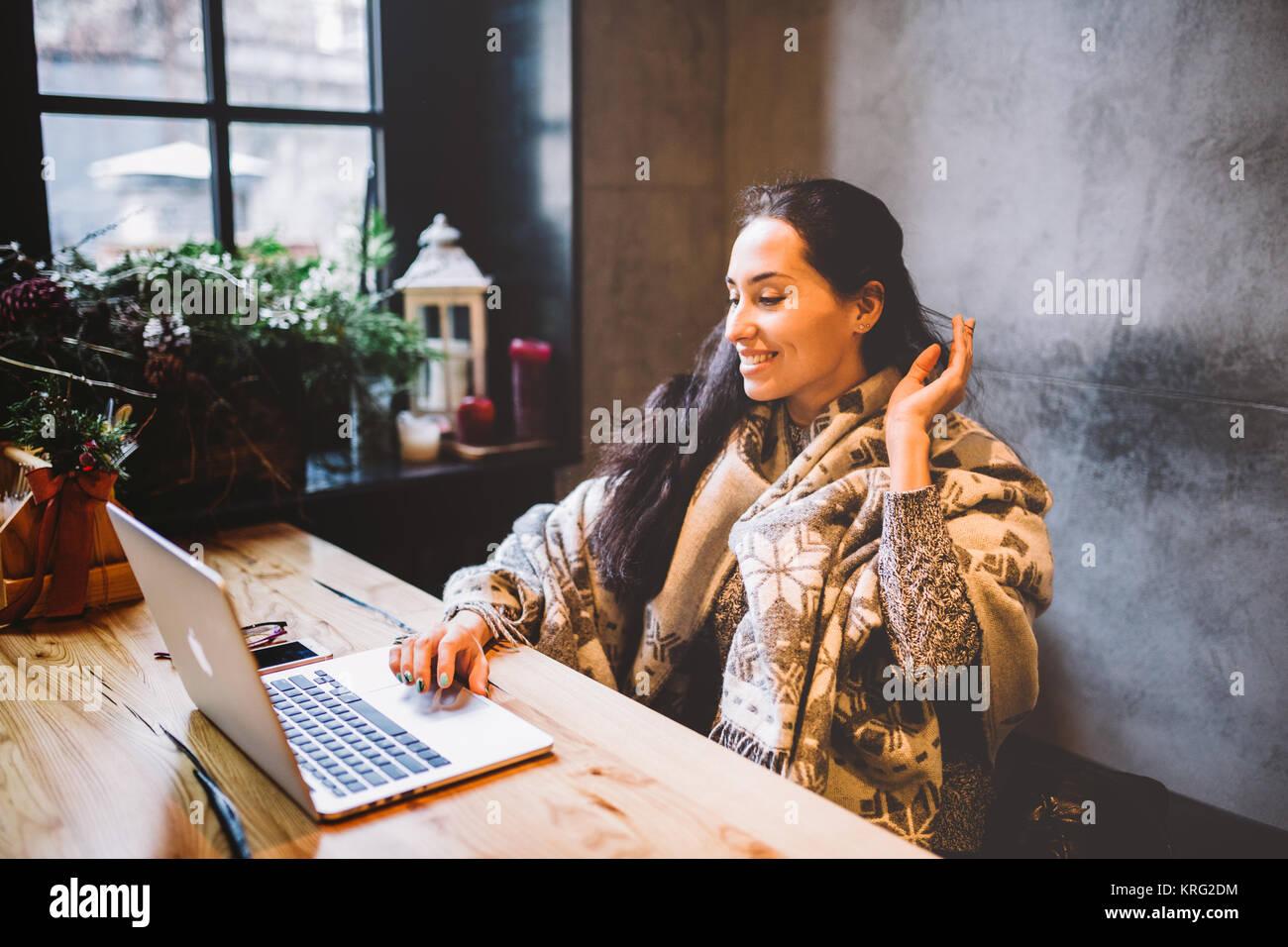 Schöne junge Mädchen nutzt laptop Technik, Typen text am Monitor in einem Café auf der Suche durch Stockbild