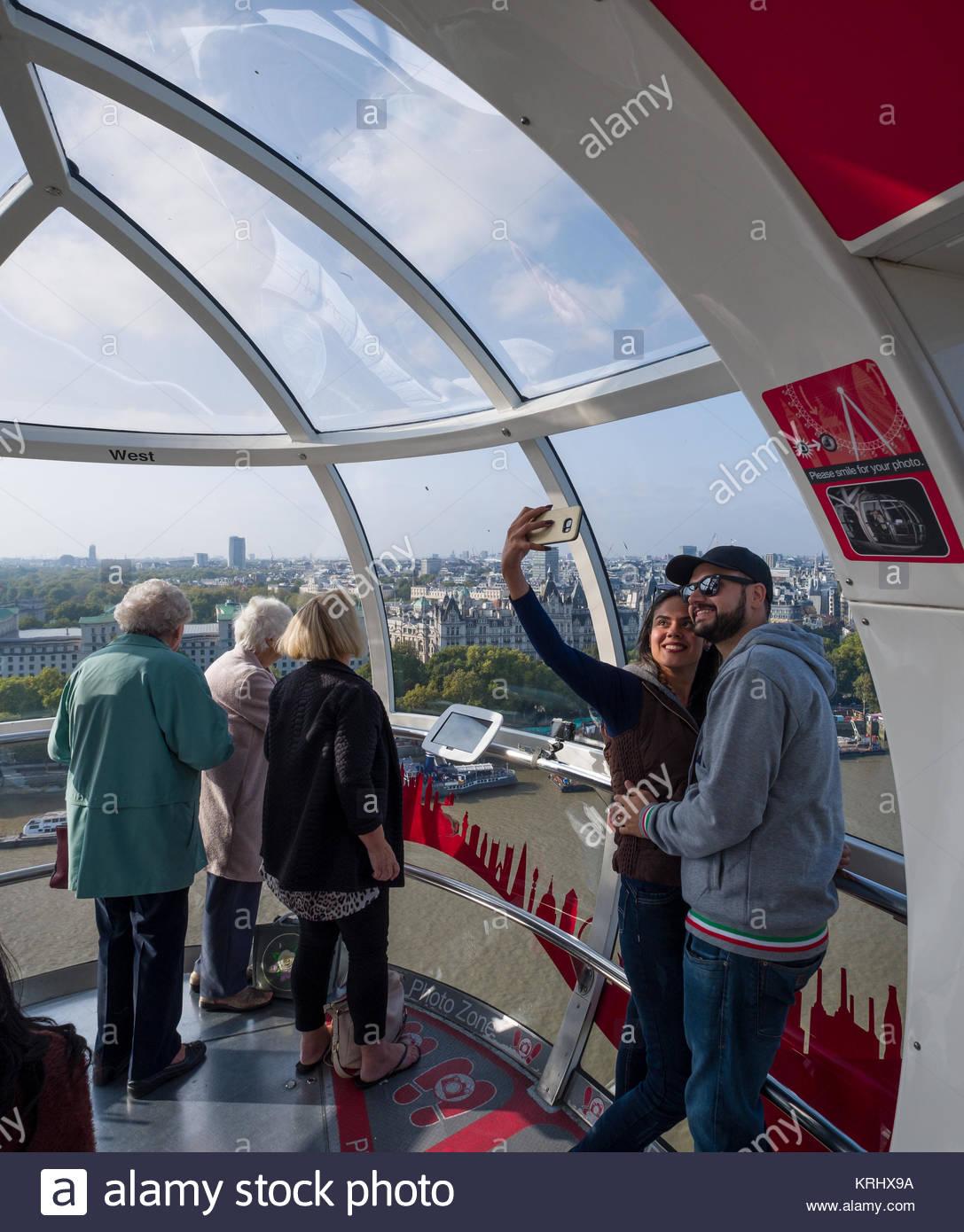 Frau mit Smartphone für eine selfie innen Passagier Kapseln des London Eye Coca-Cola über der Themse, Stockbild