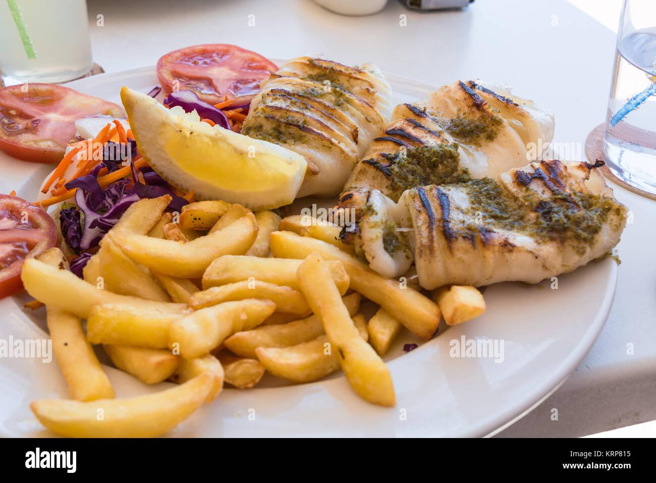 Gegrilleten Oktopus. Gegrilleter Tintenfisch serviert mit Pommes frittes und Zitronen und Salat. Stockbild