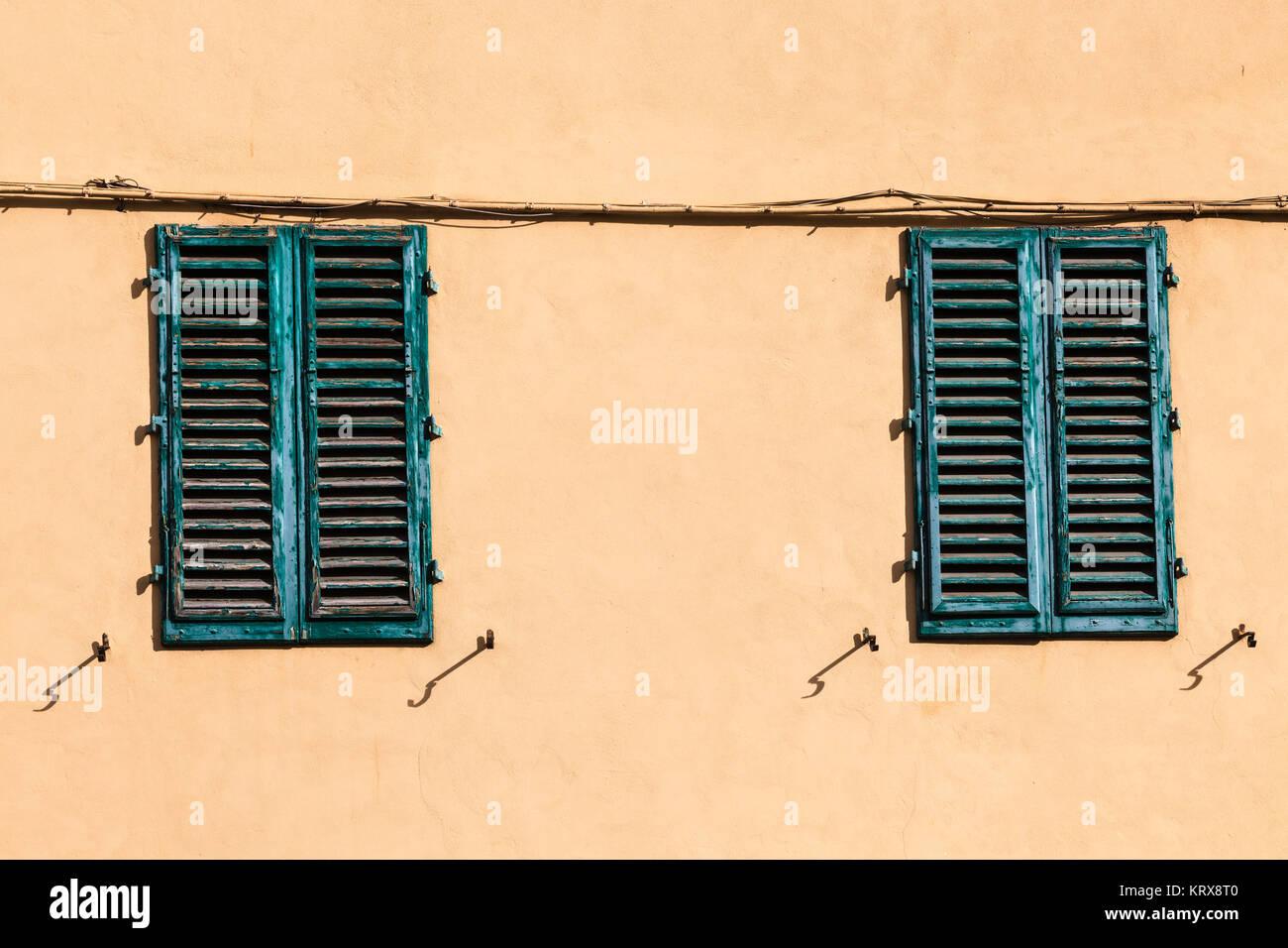 Geschlossene grüne Windows auf gelbe Wand von altes Haus Stockbild