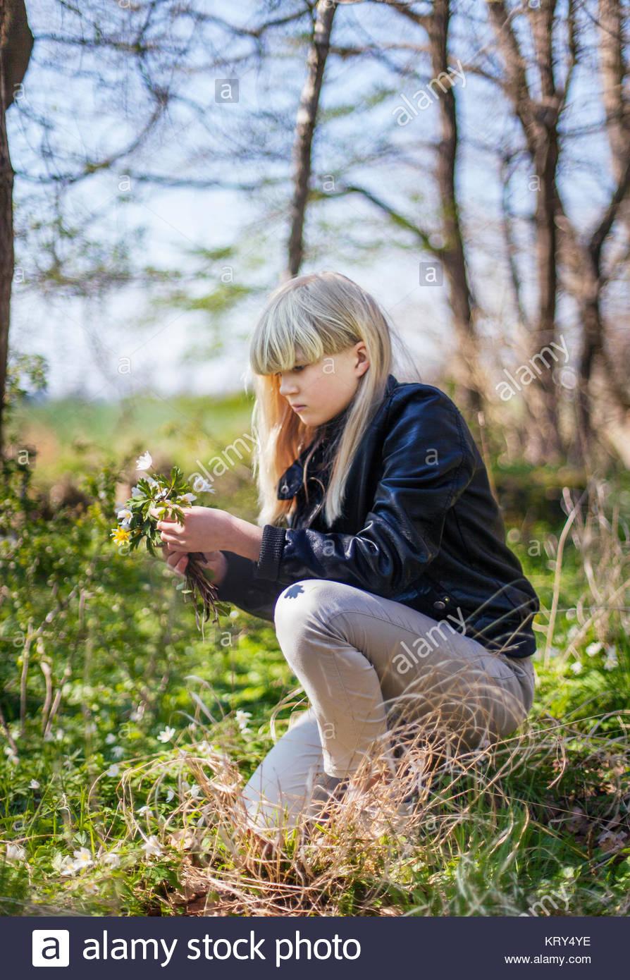 Mädchen sammeln Blumen an einem Wald Stockbild