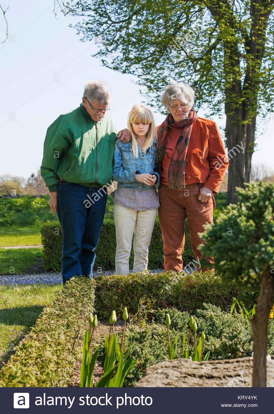 Mädchen und ihre Großeltern in Kirchhof Garten Stockbild