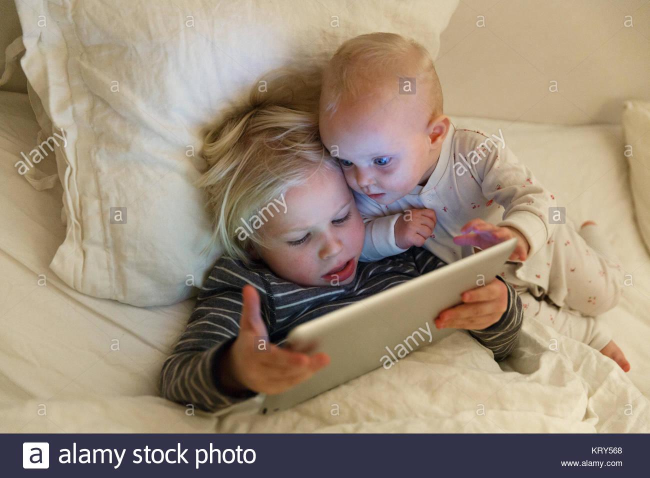 Kinder mit einem Tablet im Bett Stockbild