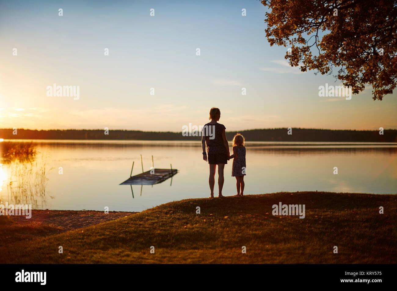 Mutter und Tochter von See bei Sonnenuntergang Stockbild