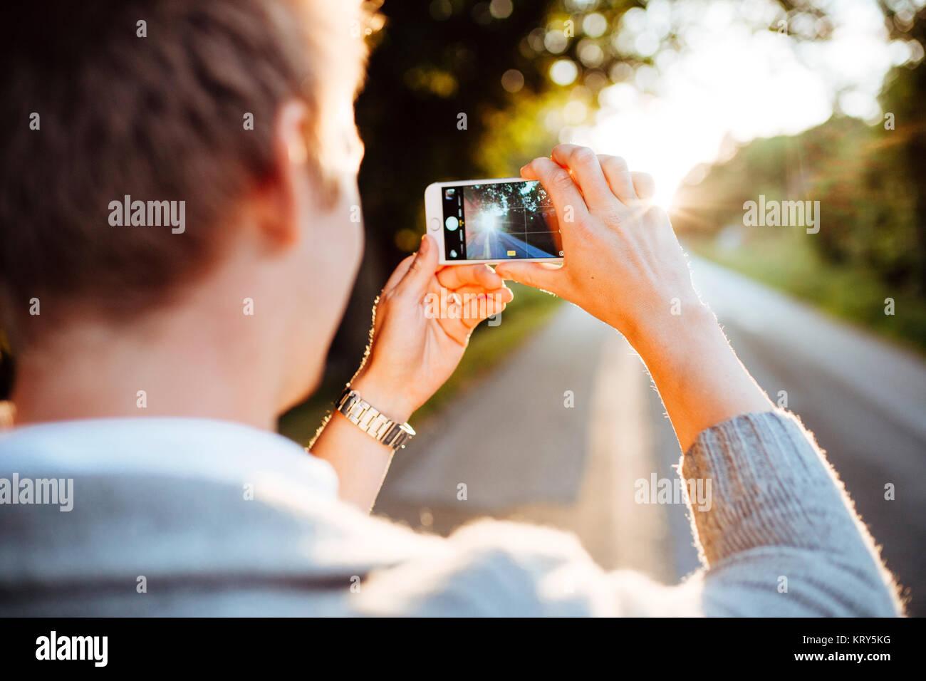Mann Fotografieren einer Straße bei Sonnenuntergang in Bohuslan, Schweden Stockbild
