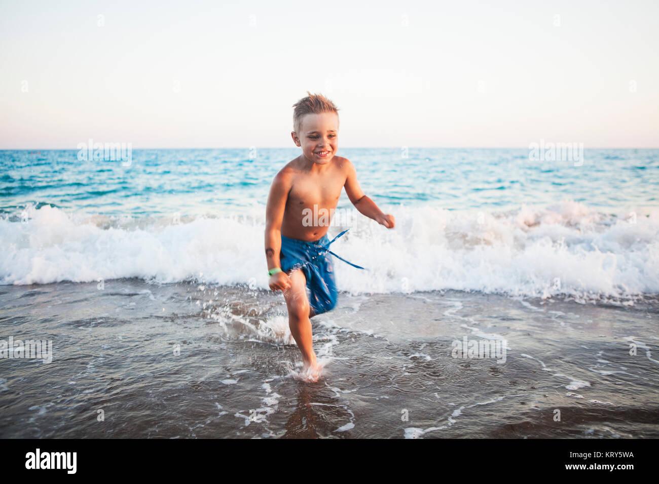 Ein Junge spielt in der Brandung am Strand in der Türkei Stockbild