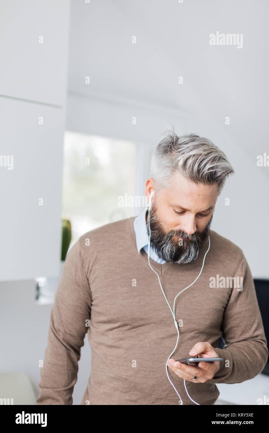 Ein Mann mit Ohrhörer im Hören auf sein Handy Stockbild