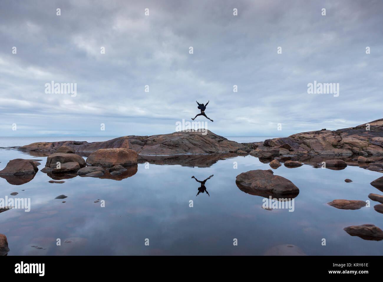 Frau springen auf Rock am See im Vasterbotten, Schweden Stockfoto