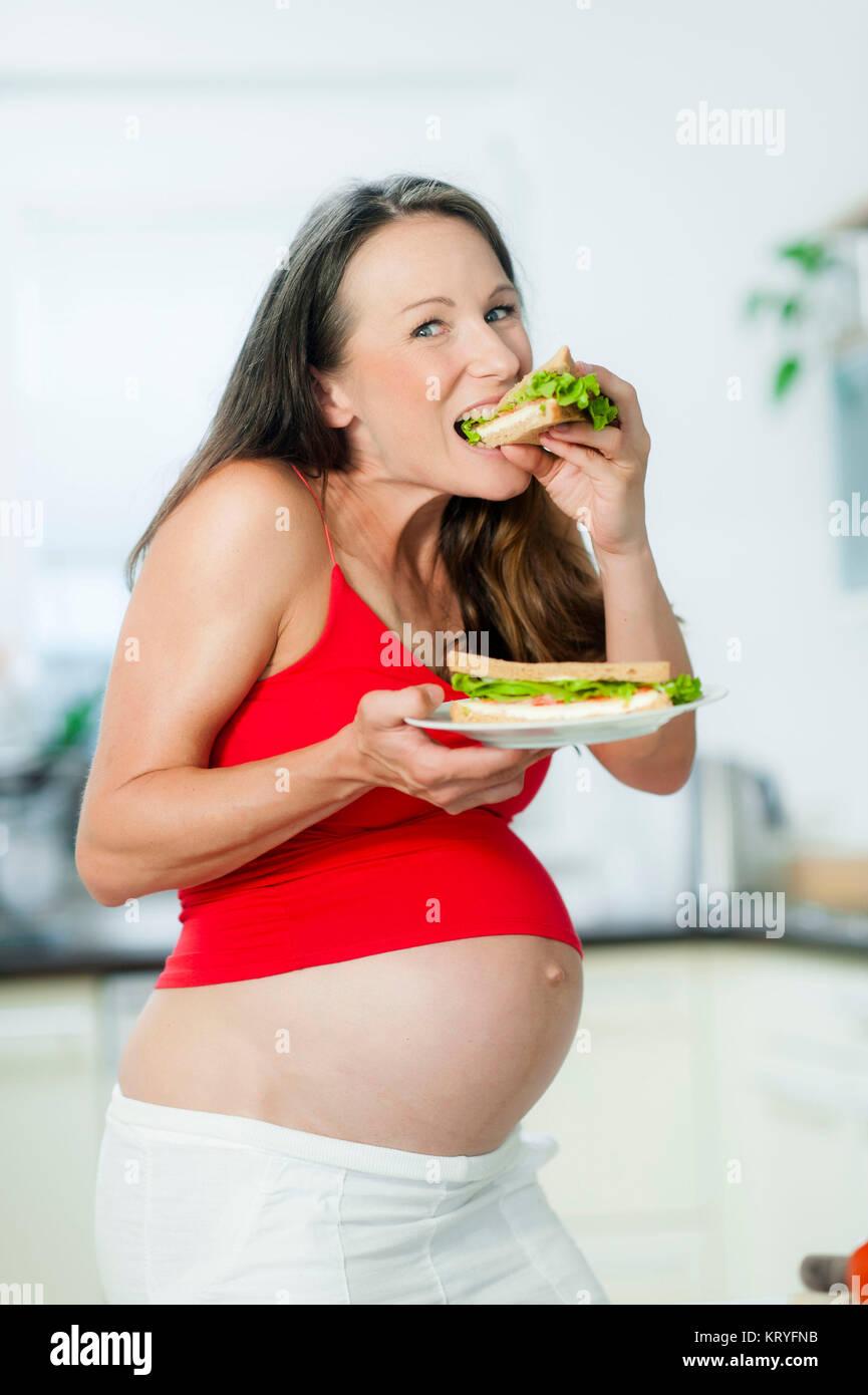 Schwangere Frau isst ein Sandwich - schwangere Frau isst ein Sandwich Stockbild