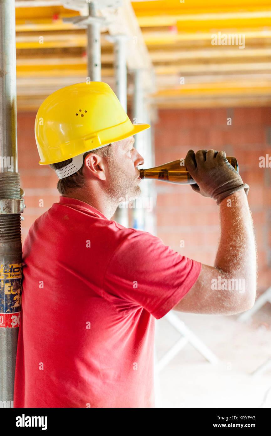 Bauarbeiter mit Bierflasche am Bau-Gebäude Arbeiter mit Bier Flasche im Gebäude Los Stockbild