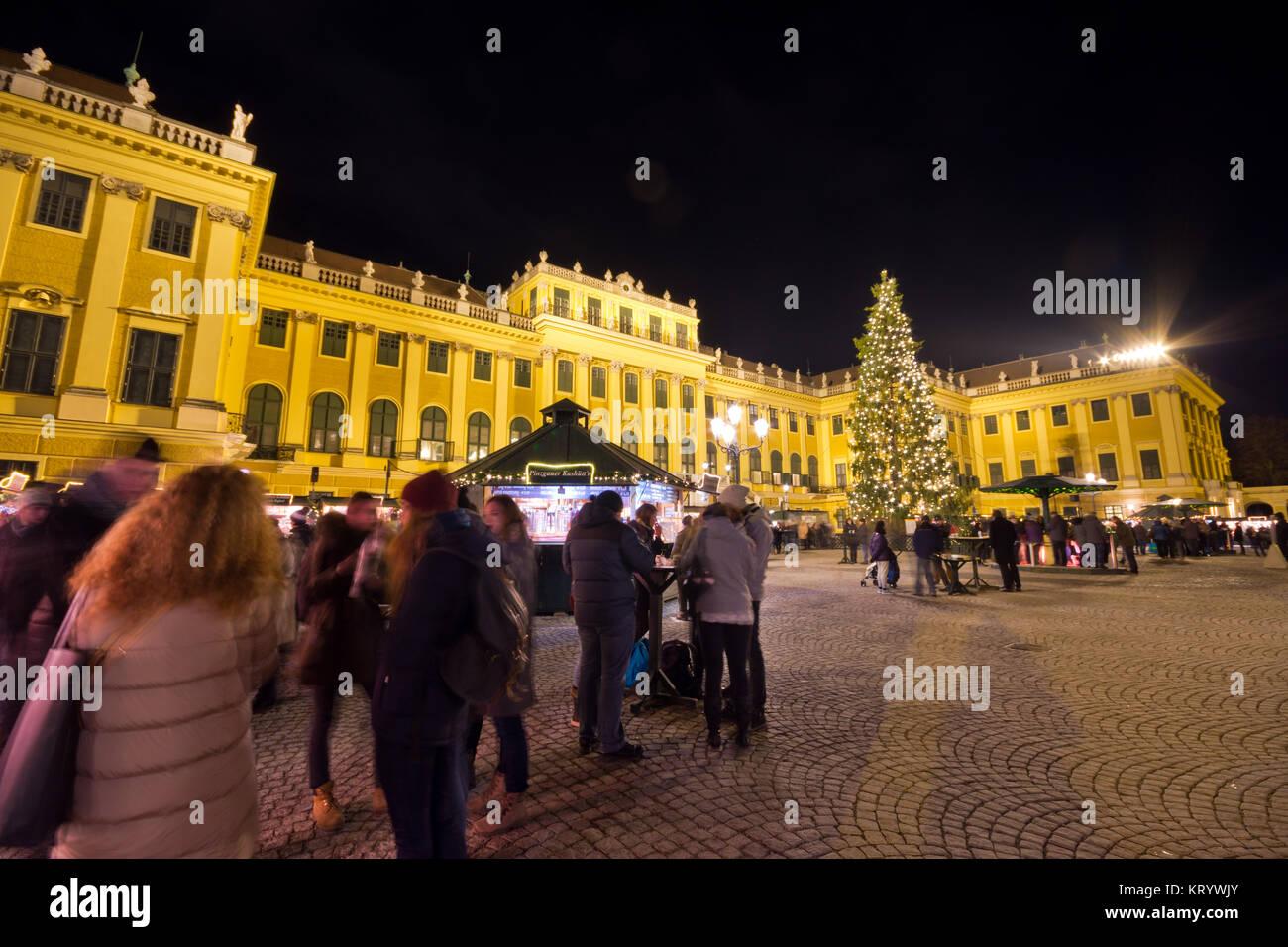 Traditioneller Weihnachtsmarkt mit beleuchteten Schloss Schönbrunn und Lichterketten geschmückten Weihnachtsbaum Stockbild