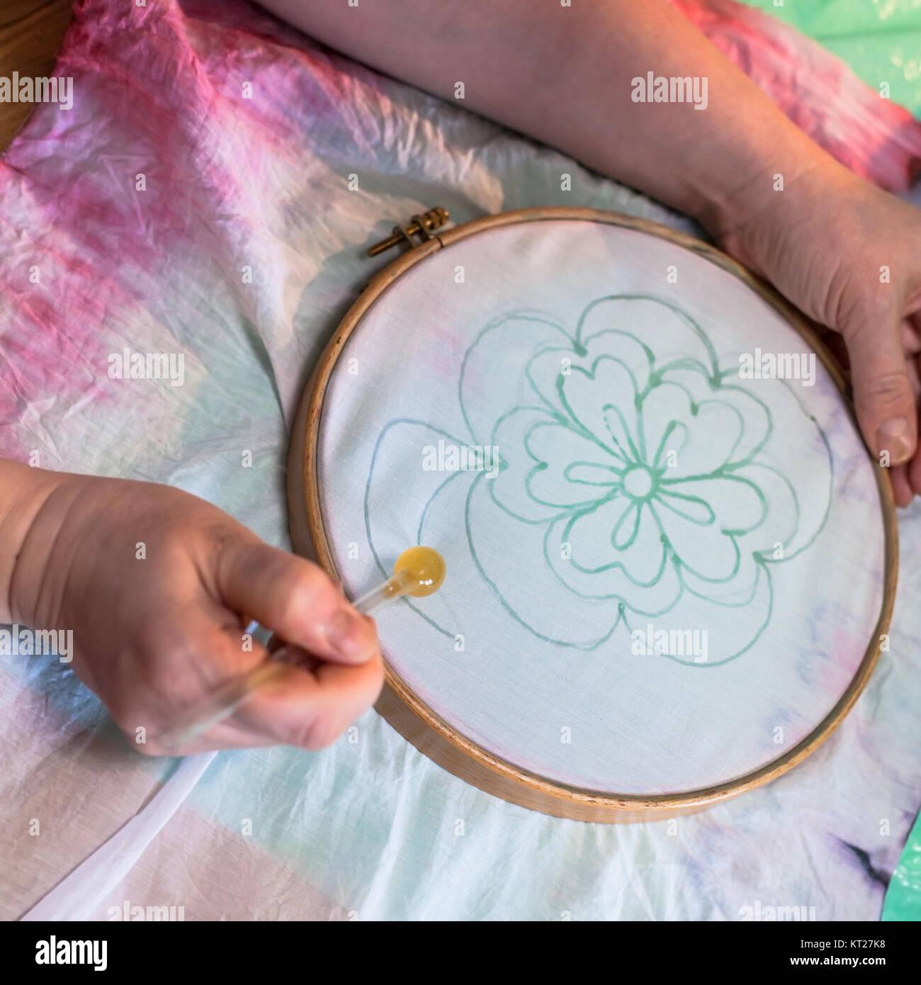Künstler zeichnet die Kontur der Blume auf Batik Stockbild