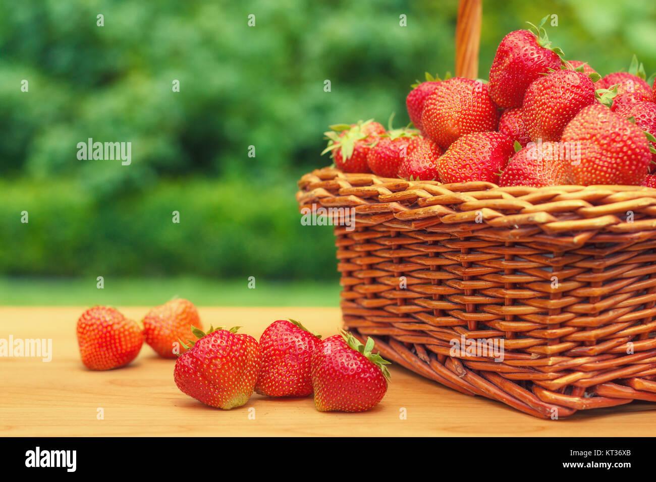 frische erdbeeren in einem korb auf h lzernen tisch im. Black Bedroom Furniture Sets. Home Design Ideas