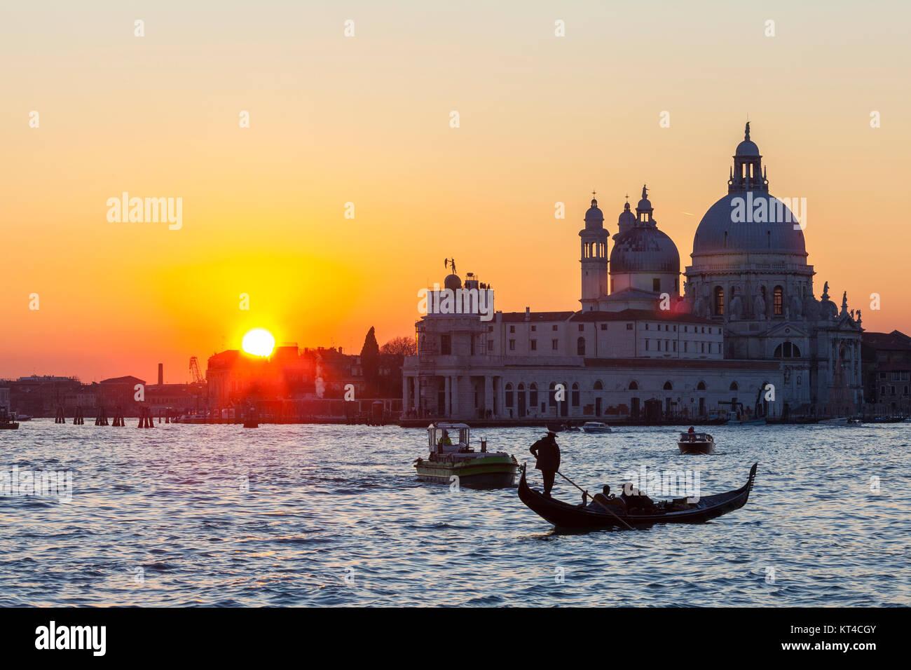 Bunte orange Sonnenuntergang über der Lagune von Venedig und der Basilika di Santa Maria della Salute mit Booten Stockbild