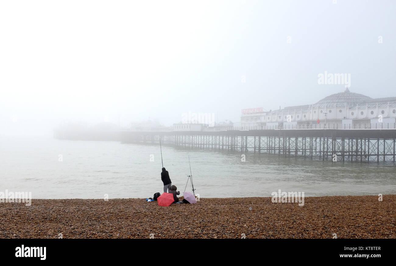 Brighton, UK. 22 Dez, 2017. Ein Fischer können nicht weit auf das Meer sehen von der Palace Pier Brighton an Stockbild