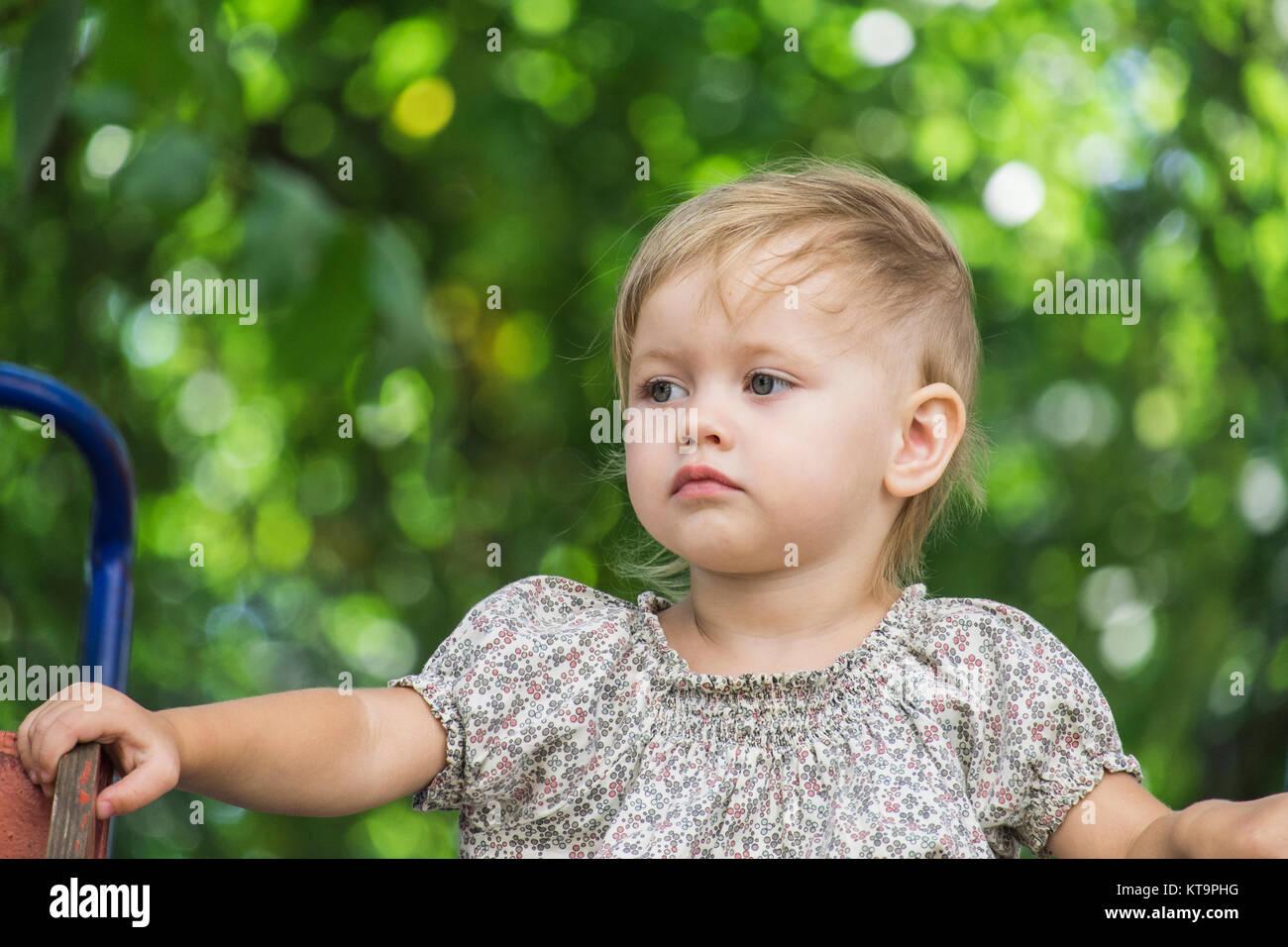 Baby sitzt auf einem Hügel. Hinter dem verschwommenen Hintergrund von grünen Bäumen, Stockbild