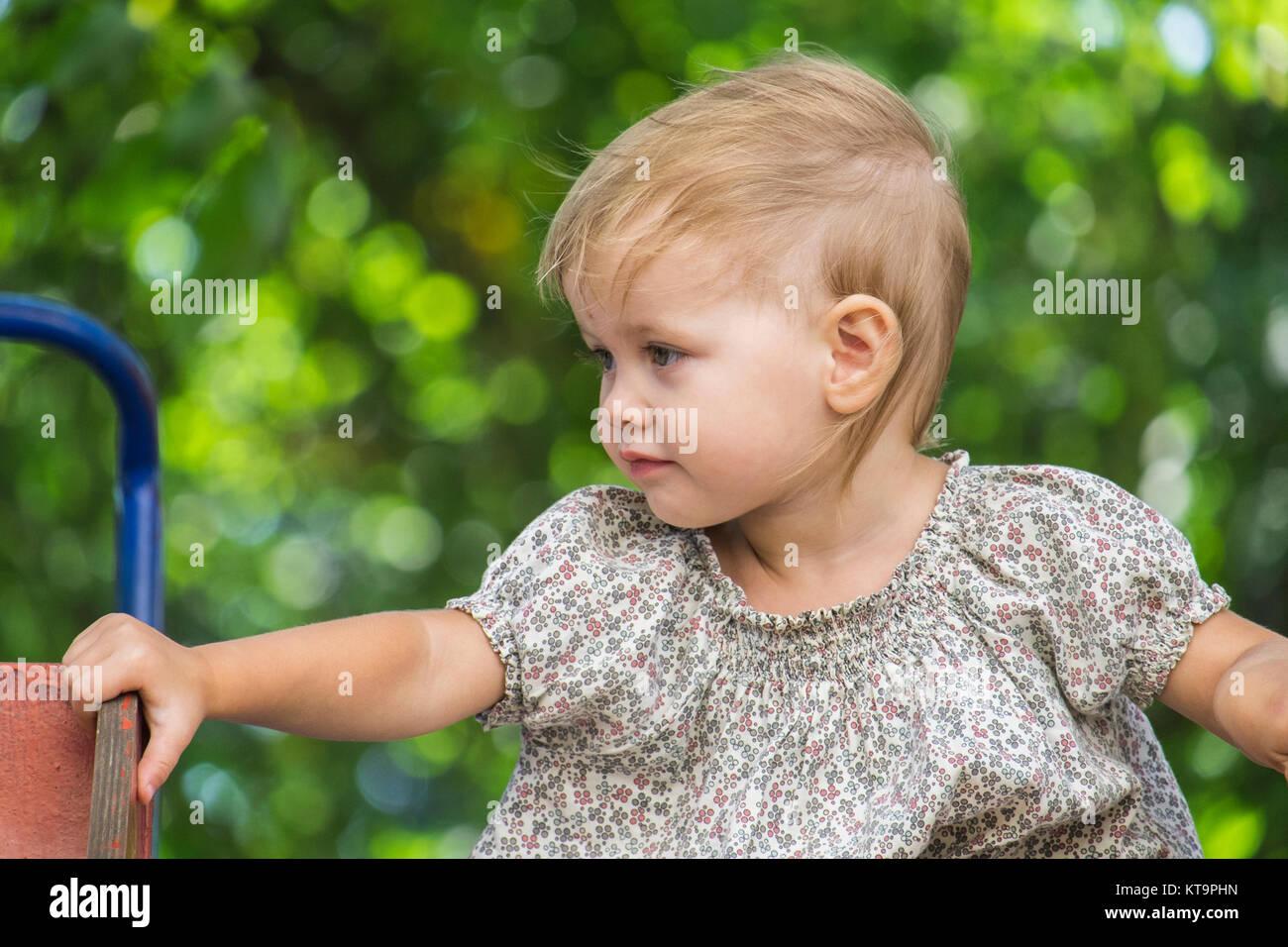 Baby sitzt auf einem der Kinder schieben und auf der Suche nach rechts Stockbild