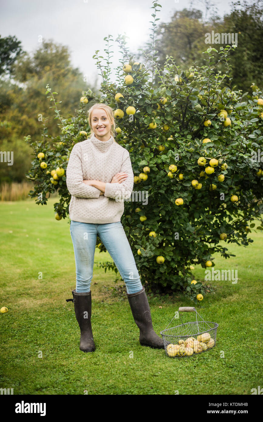 Portrait von lächelnden jungen Frau an Quitte Baum im Garten Stockbild