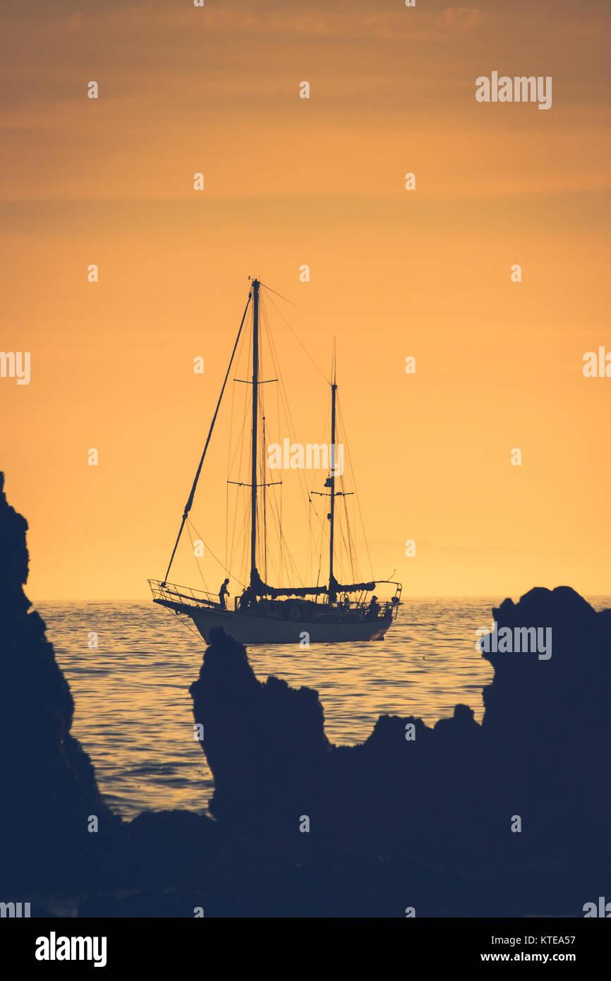 Silhouette einer Segelboot bei Sonnenuntergang Segeln von Newport Beach, Kalifornien mit Santa Catalina Insel im Stockfoto