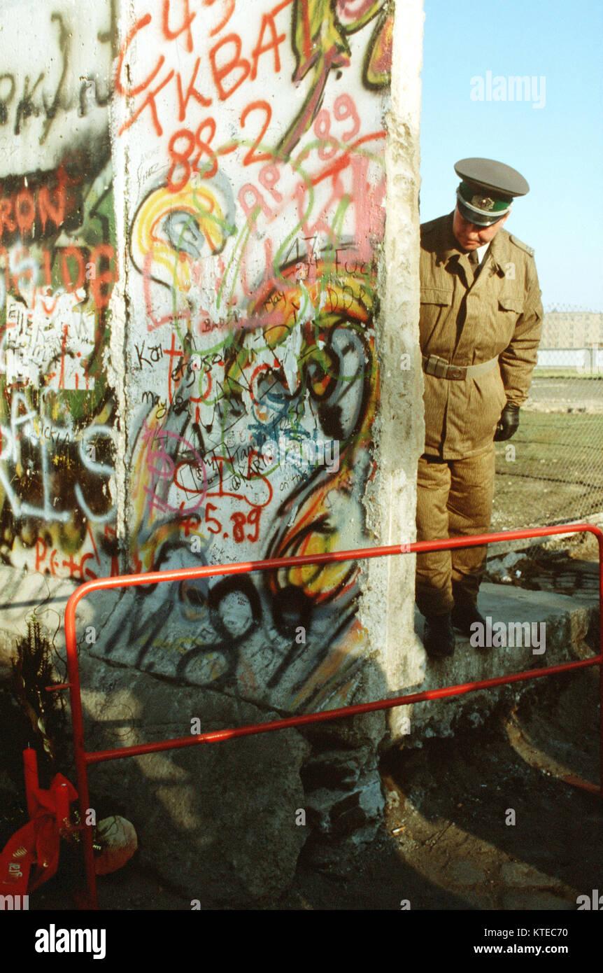 Ein Ostdeutscher Polizist schaut auf einen kleinen Weihnachtsbaum schmücken die Westdeutsche Seite der Berliner Stockbild