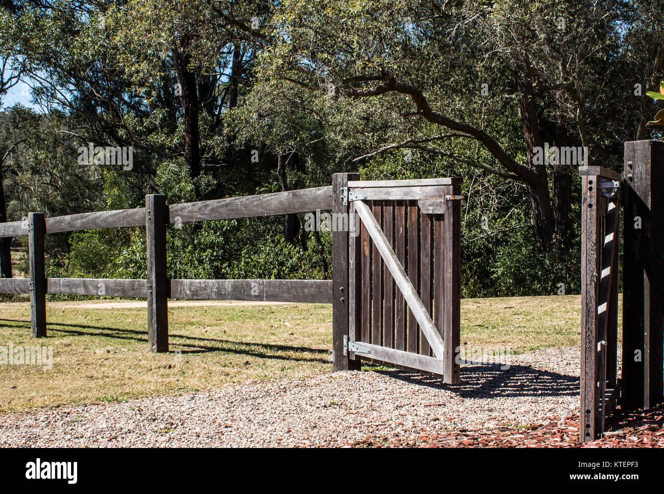 Holz- ländlichen Zaun mit Tor im Sonnenschein mit Bäumen im ...