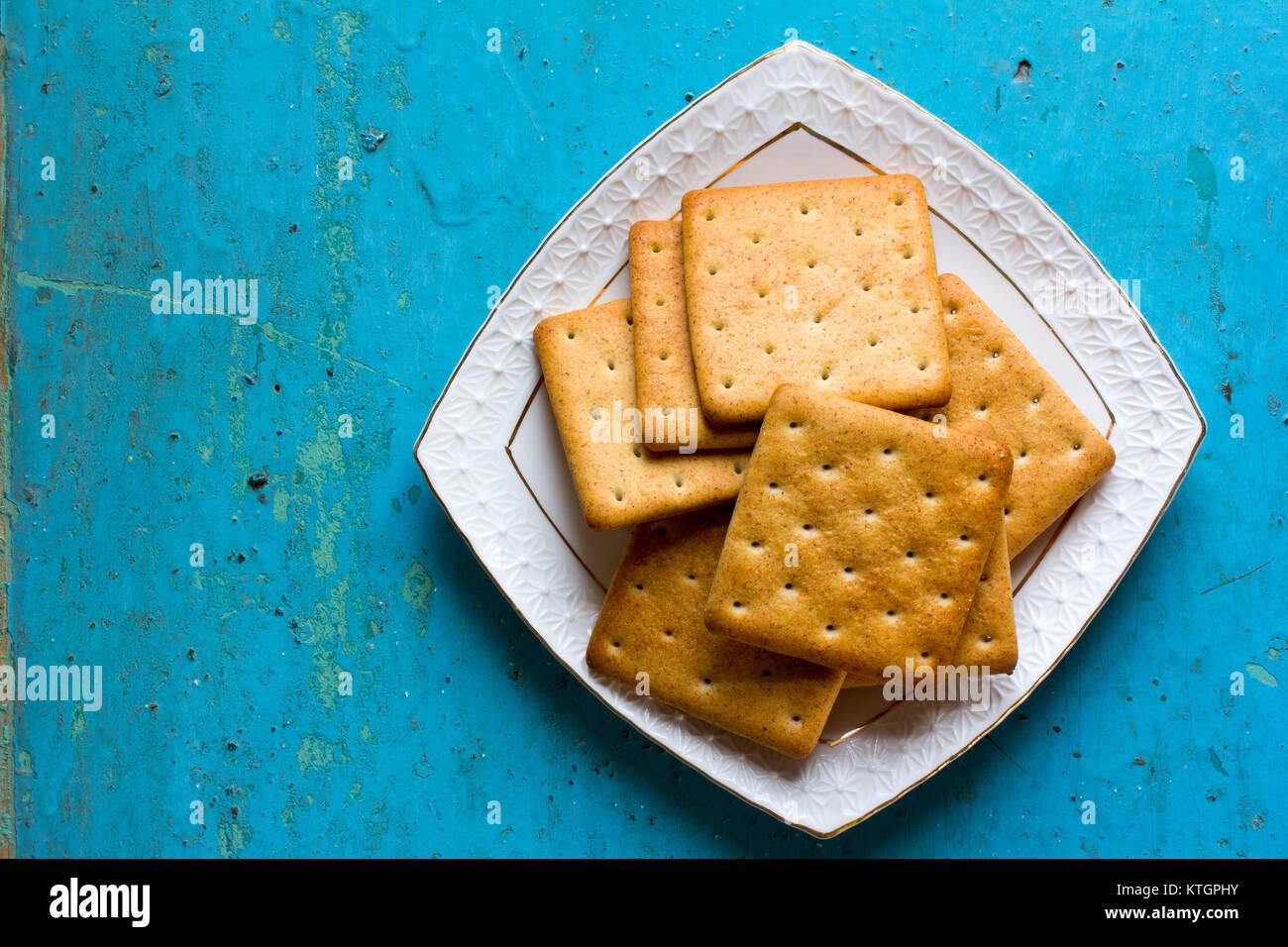 Cracker Kekse in eine weiße Keramik square Untertasse auf alten blauen Hintergrund. Freier Platz für Text. Stockbild