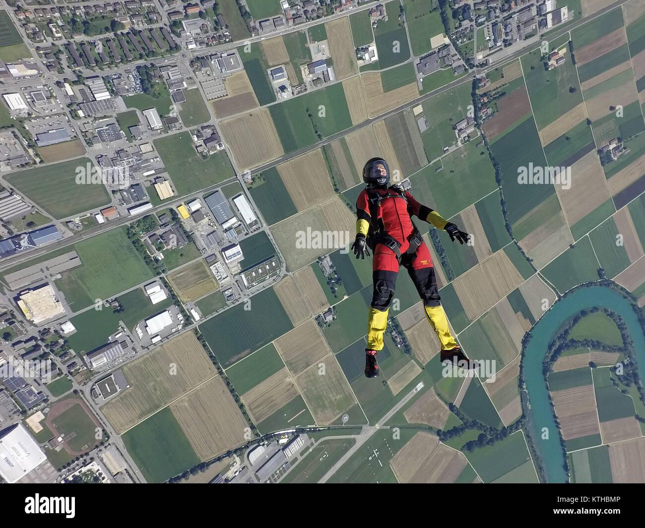 In diesem Fallschirmspringen Mädchen, die Verfolgung auf dem Rücken über eine schöne Landschaft Stockbild