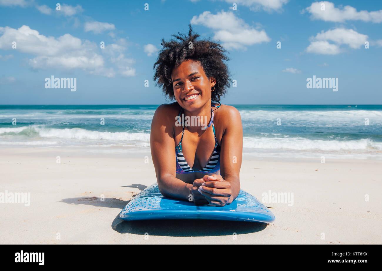 Surfer Girl mit Afro Frisur lächelnd, liegend auf blauem Surfbrett auf dem weißen Sand am Dreamland Beach, Stockbild