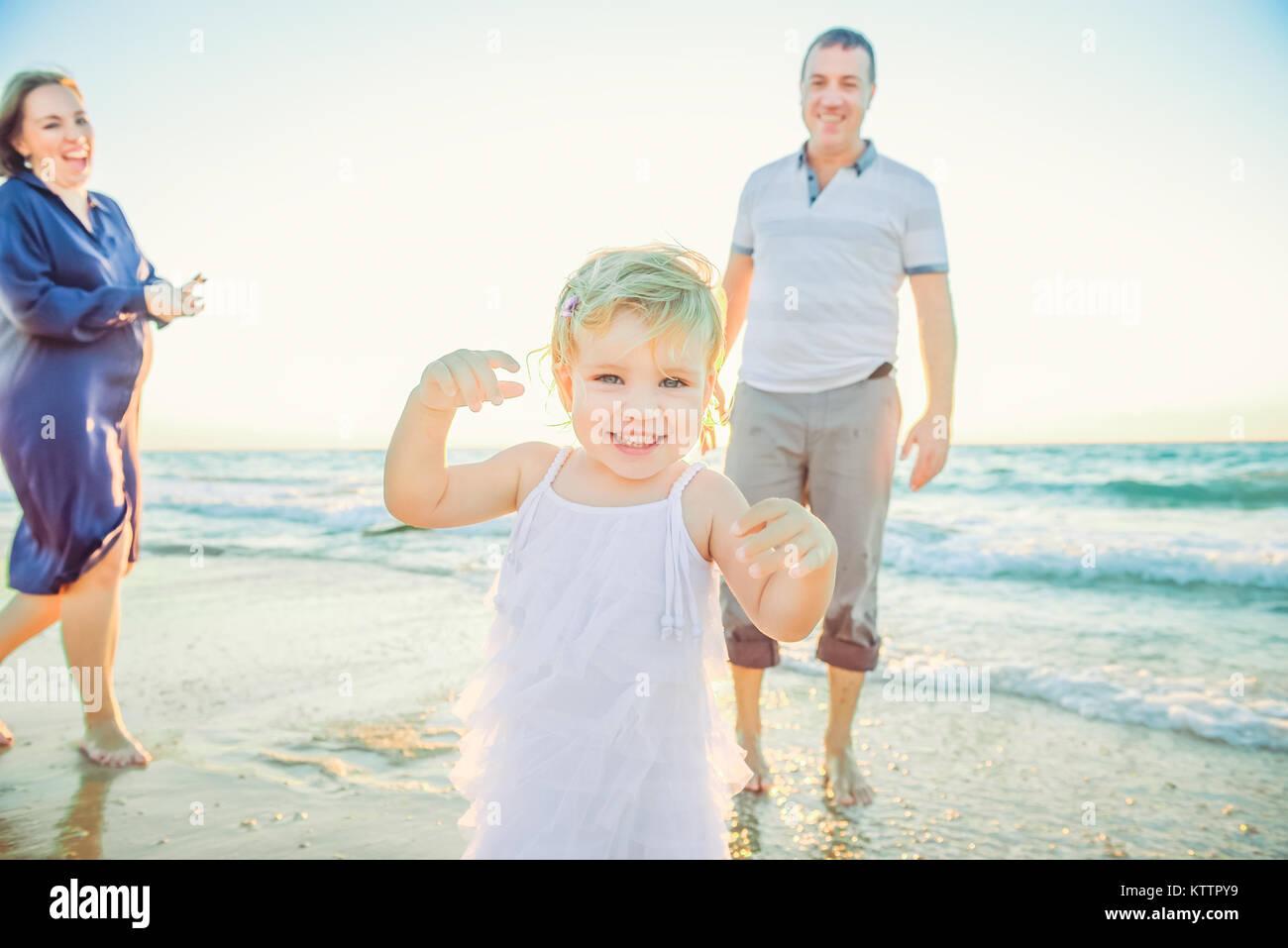 Lachendes Baby girl vorwärts läuft mit lachenden Eltern im Hintergrund. Glück und Harmonie in der Stockbild