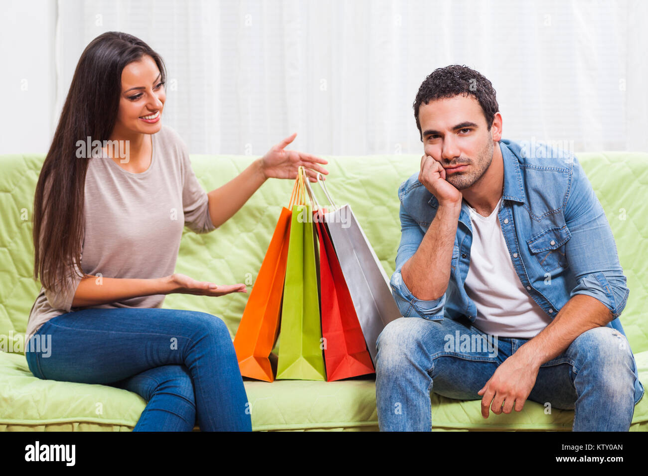 Junges Paar sitzt auf einem Sofa zu Hause. Der Mensch ist sich über ...