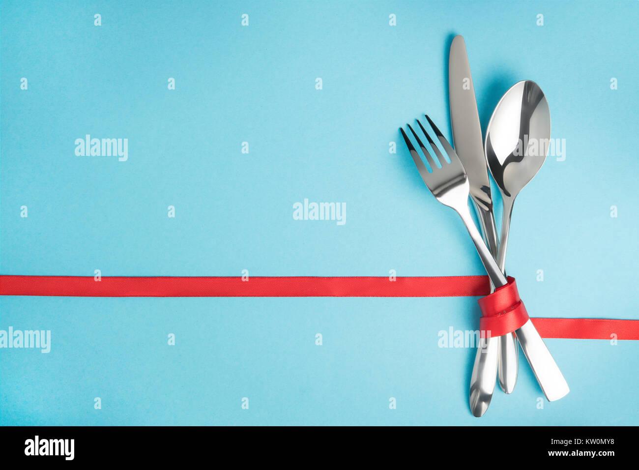Gabel, Löffel und Messer mit einem roten Band auf blauem Hintergrund ...