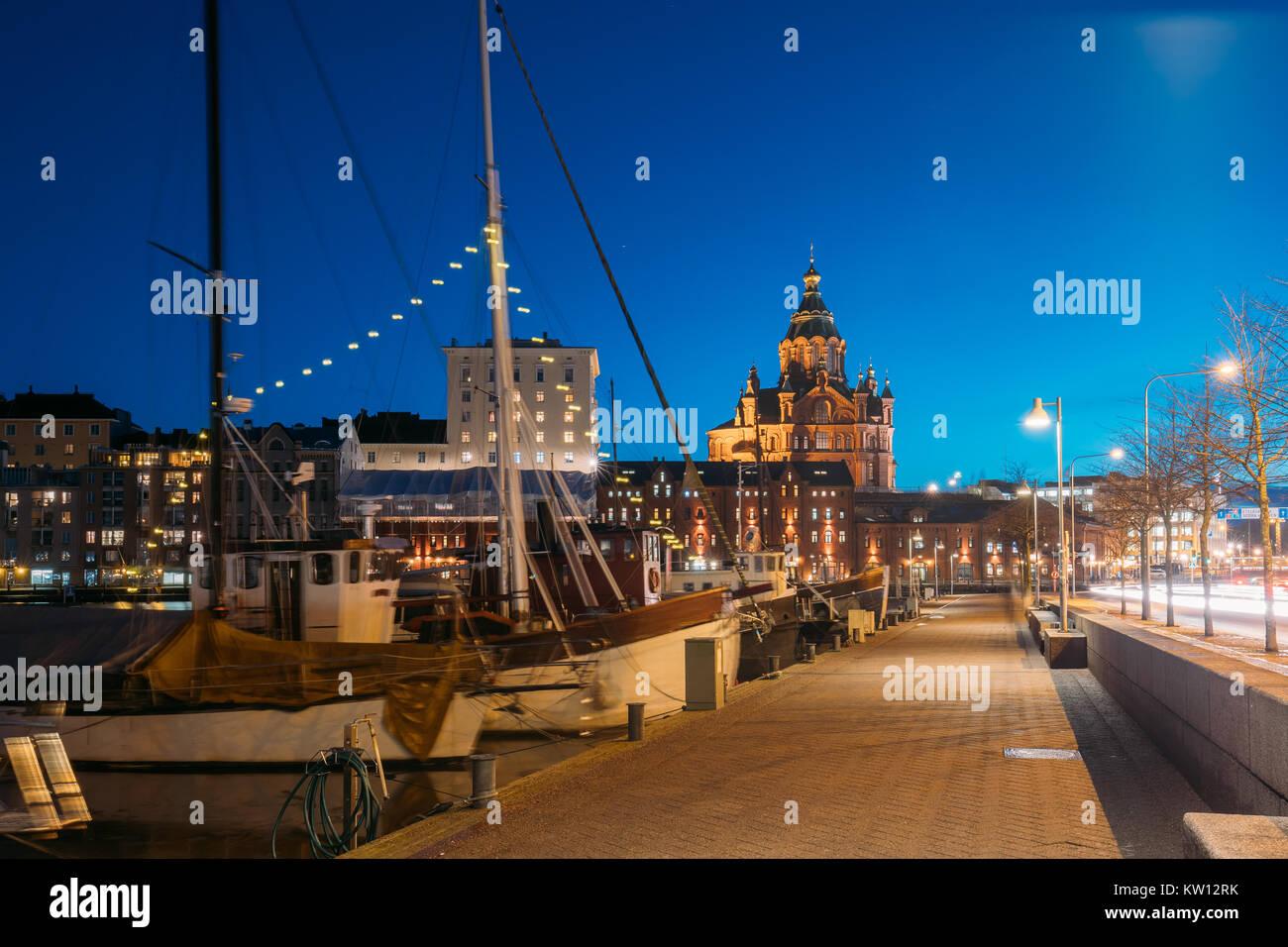 Helsinki, Finnland. Pier mit Booten, Pohjoisranta Straße und Blick auf die Uspenski Kathedrale in Abend Nacht Stockbild