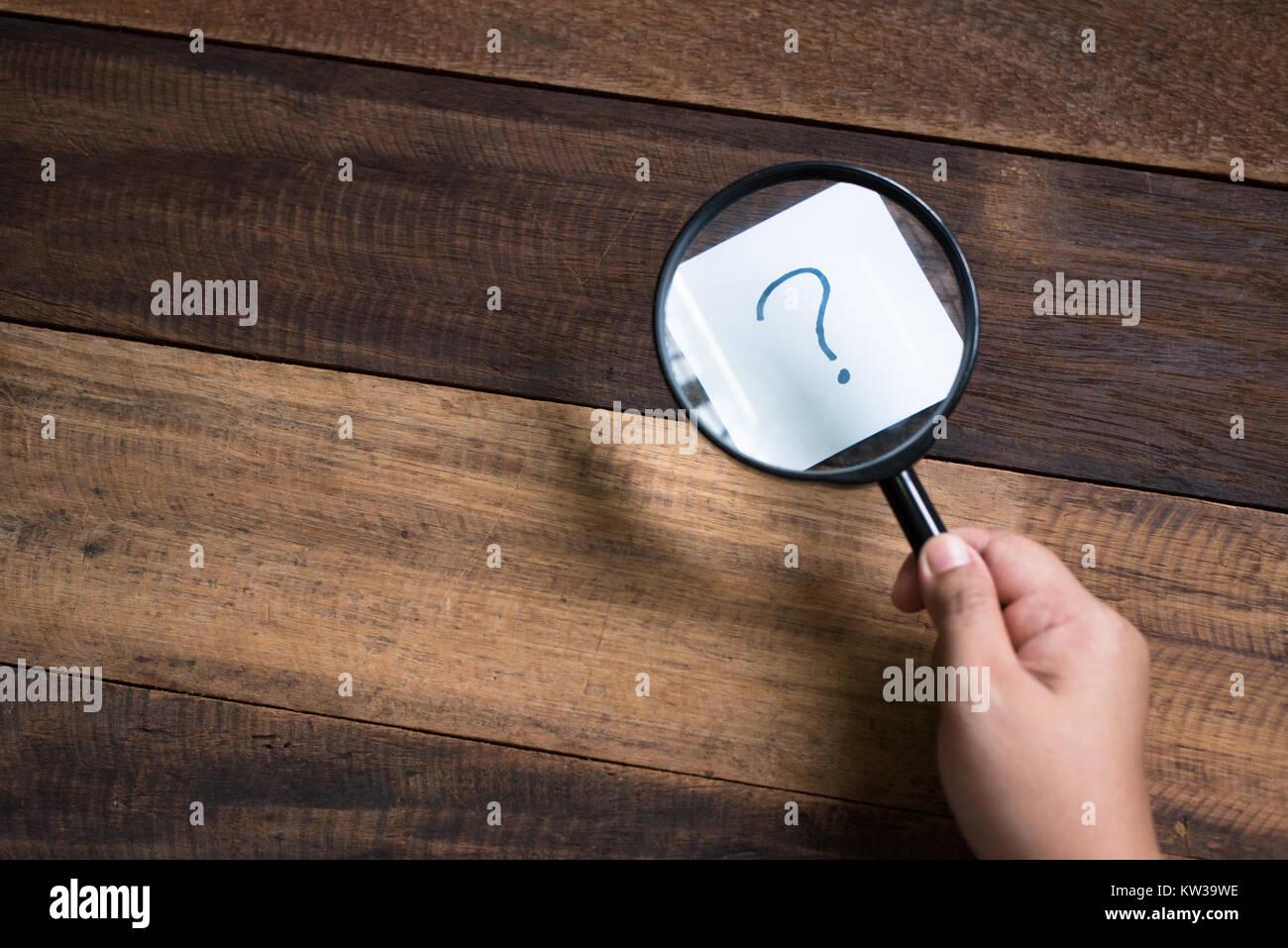 Hand mit Lupe mit Schwerpunkt auf Fragezeichen. Geheimnis und Suche Konzept Stockbild