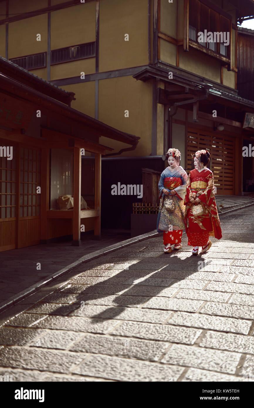 Zwei junge Maiko, Geisha Auszubildende in hellen Kimono hinunter auf einer alten Straße in Kyoto, Kyoto, Japan Stockbild