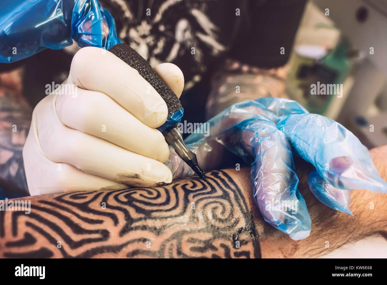 Nahaufnahme von einem professionellen Tätowierer mit Handschuhen Tätowieren ein Tribal Design auf dem linken Unterarm Stockfoto