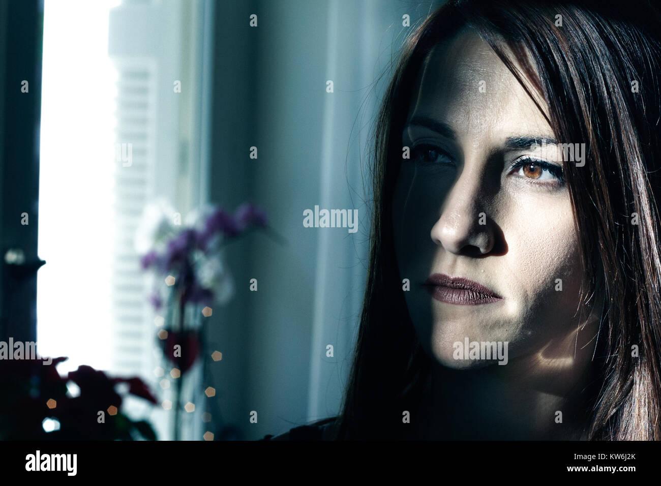 Porträt einer jungen Frau auf der Suche nach Einsamkeit zum Ausdruck bringt, nachdenklich, Low Key Licht. Stockbild