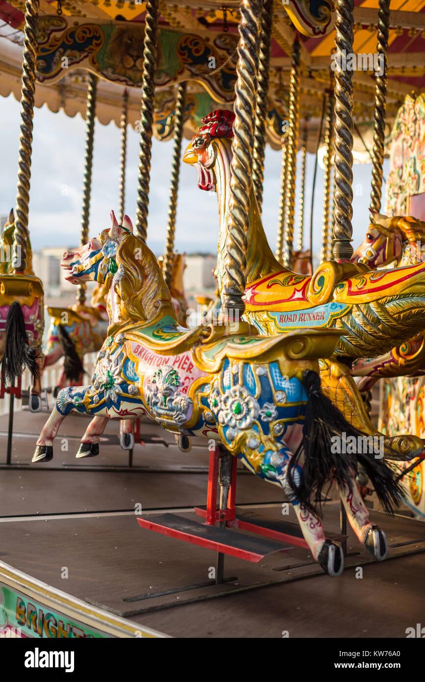 Bunt bemalte Pferde in der Abendsonne auf einem Karussell auf Brighton Pier Stockbild