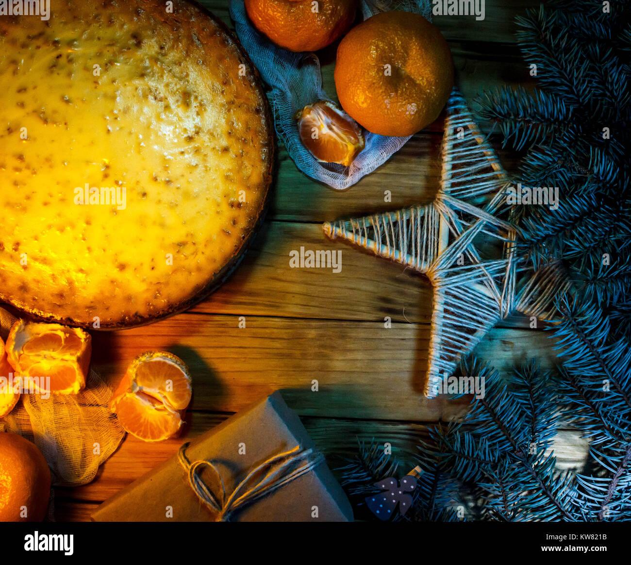 Käse Kuchen gegen Holz- Hintergrund mit Orangen, Geschenkbox und Weihnachtsdekoration. Stockbild
