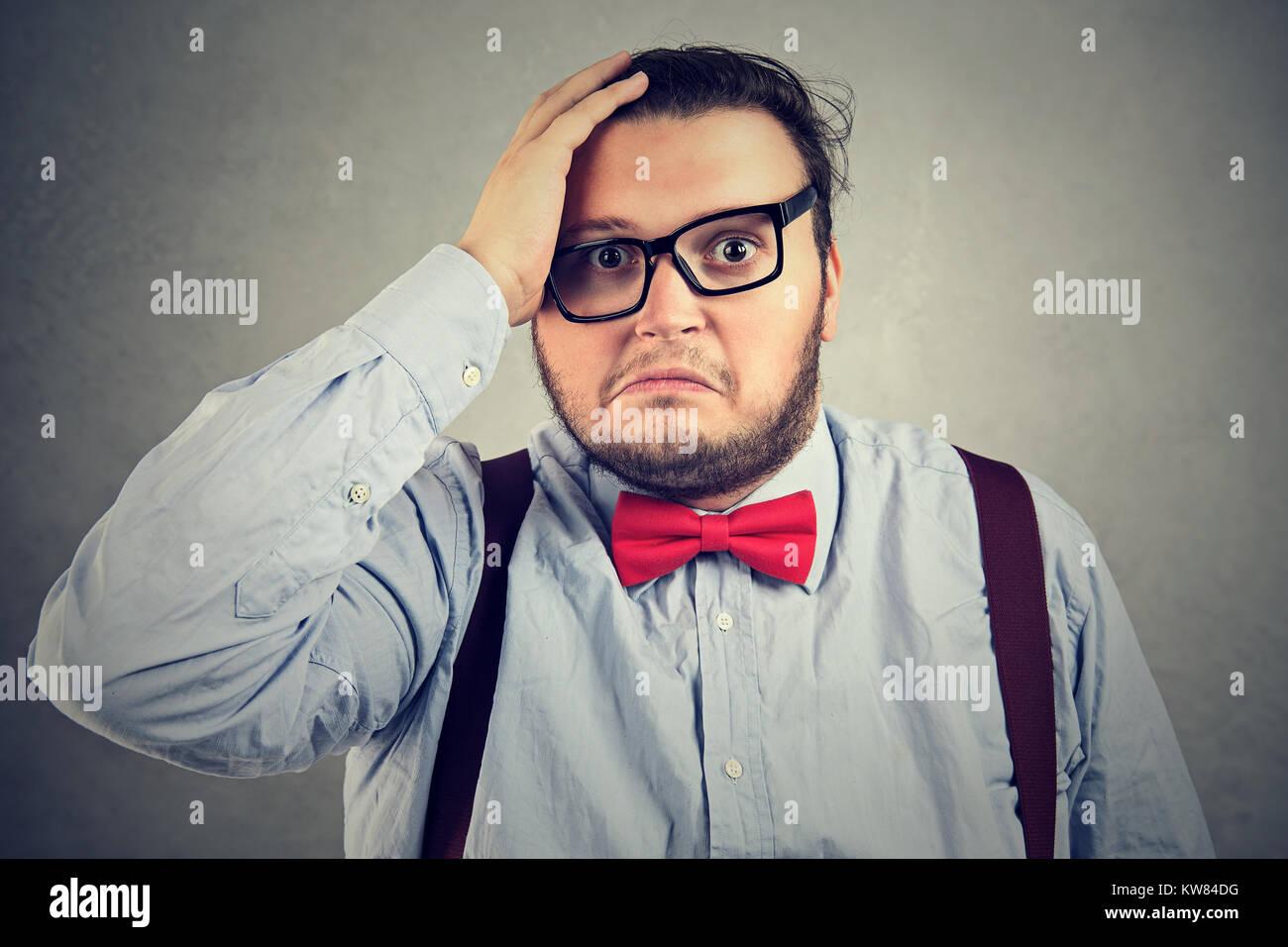 Chunky Mann verzweifelt an der Kamera auf grauem Hintergrund. Stockbild