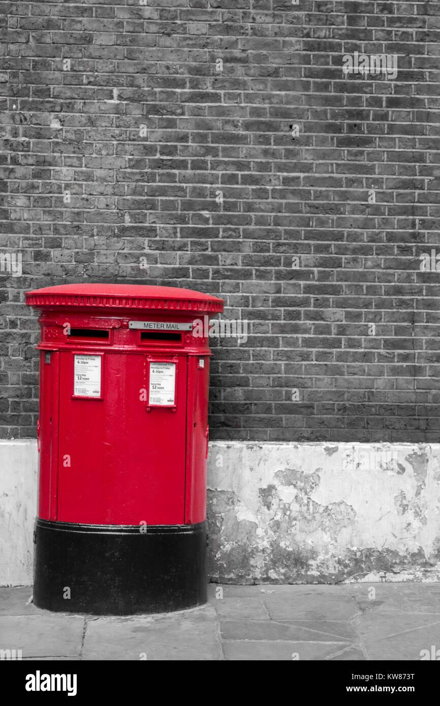 Britische Rote Post Box gegen eine Black & White B&W Mauer Hintergrund in London Stockbild