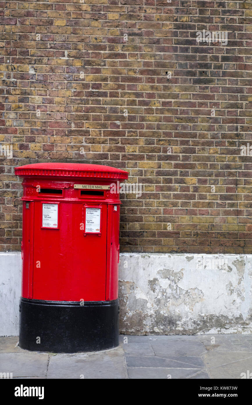 Britische Rote Post Box gegen eine Mauer Hintergrund in London Stockbild