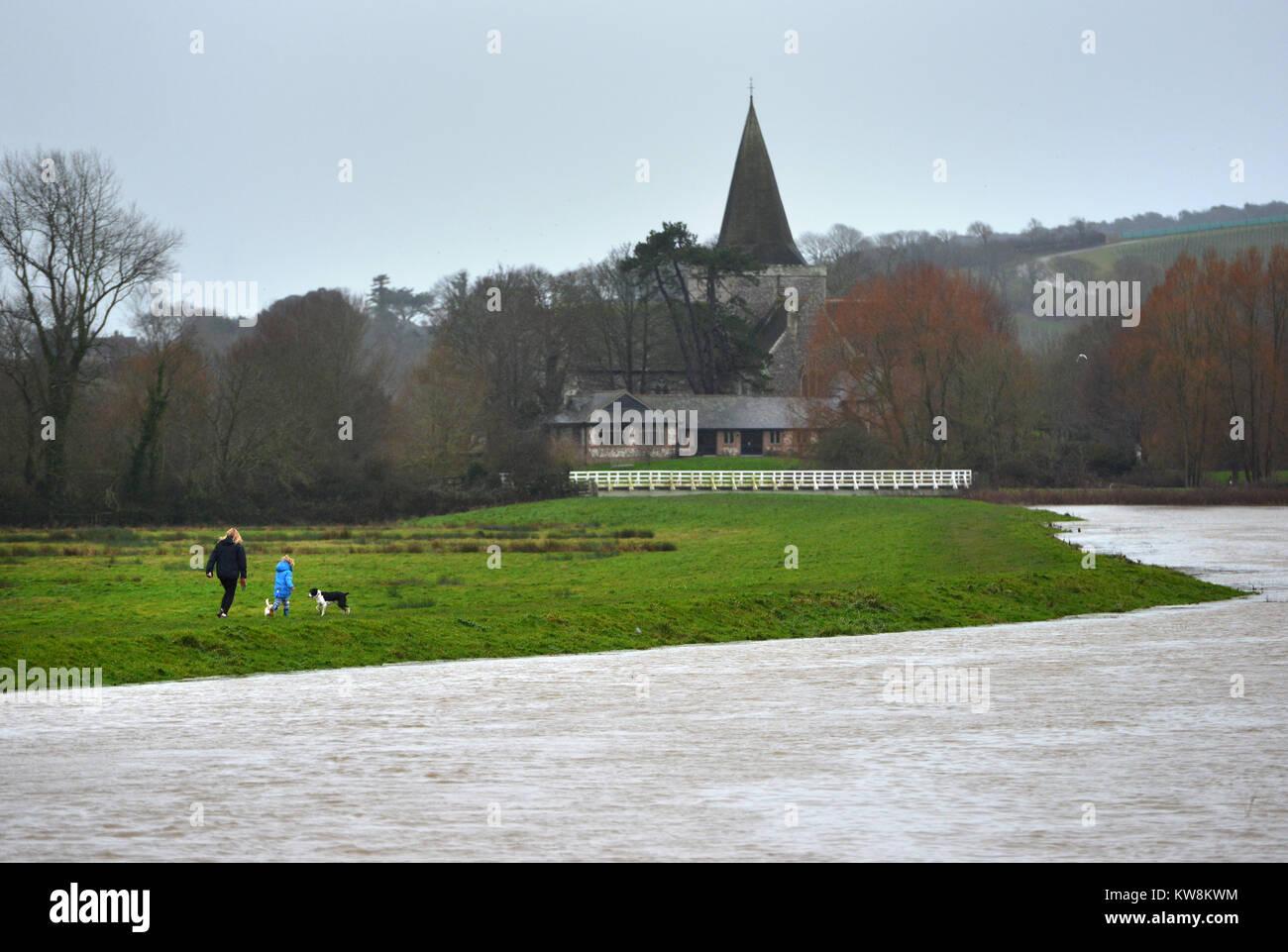 Eastbourne, East Sussex. 31. Dezember 2017. Leute, die Hunde an den Ufern der geschwollenen Cuckmere River in Eastbourne, Stockbild