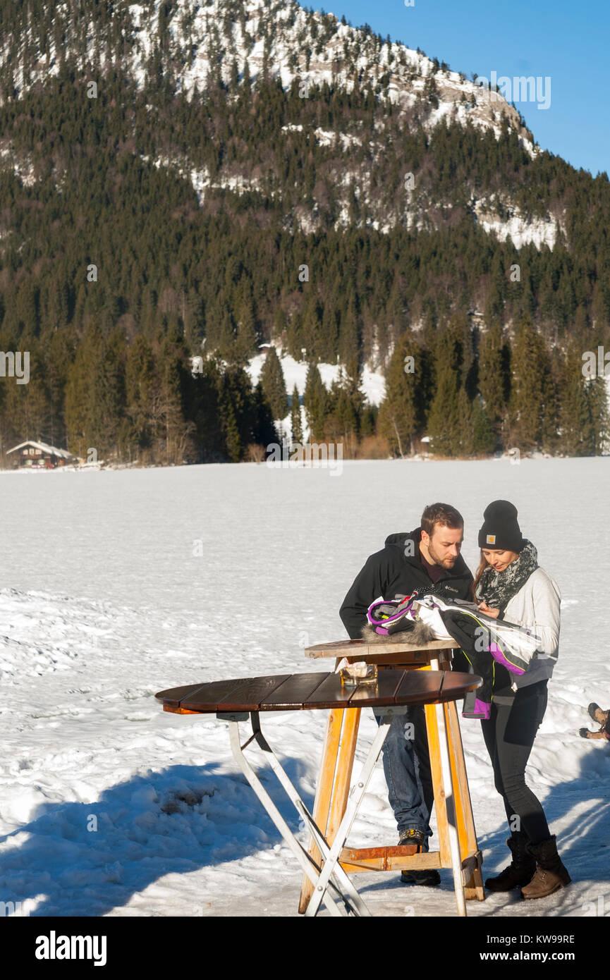 Ein paar sammelt Kräfte, während Sie Fotos an einem Tisch am See Spitzingsee München. Stockbild