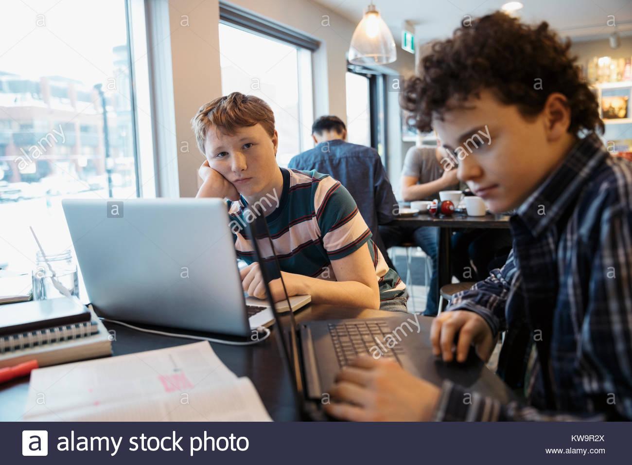 Portrait ernst High School junge Studierende an Laptop im Cafe Stockbild