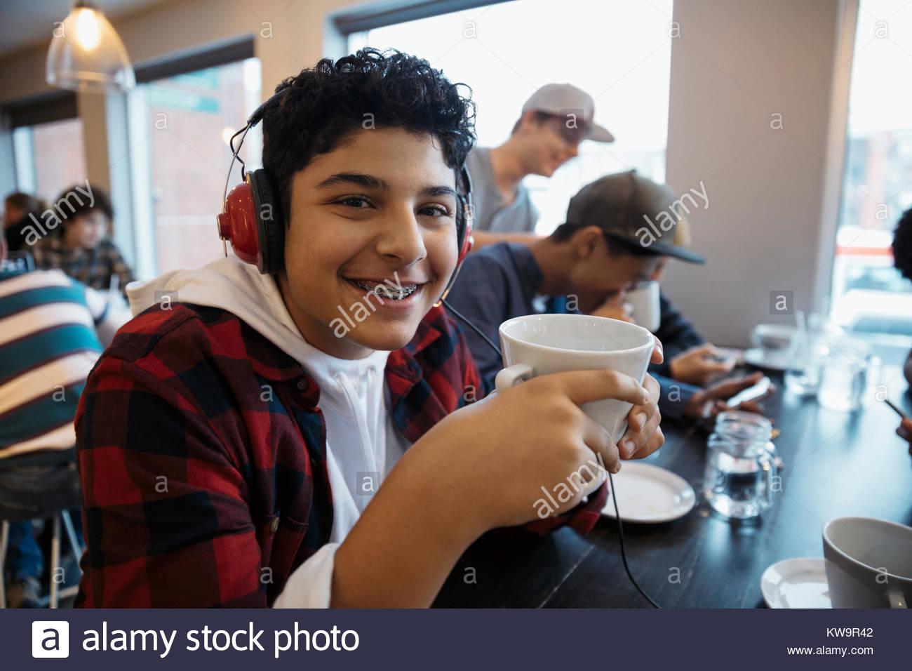 Porträt Lächeln, zuversichtlich, im Nahen und Mittleren Osten tween Junge mit Kopfhörer Kaffee trinken Stockbild